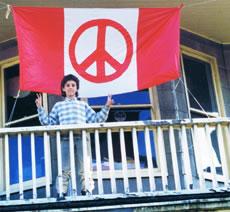 kid on balcony with peace flag