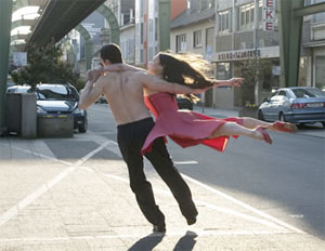 on a city street a barebacked man runs, holding a woman in midair