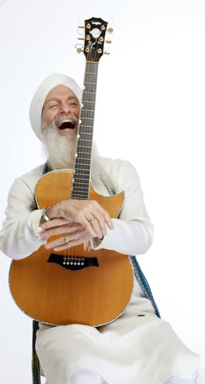 An image of the white-bearded guru holding a cutaway guitar, laughing