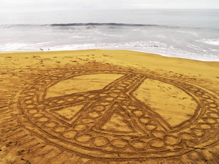 An ornate peace sign scratched into the sand on a beach with the waves in the background