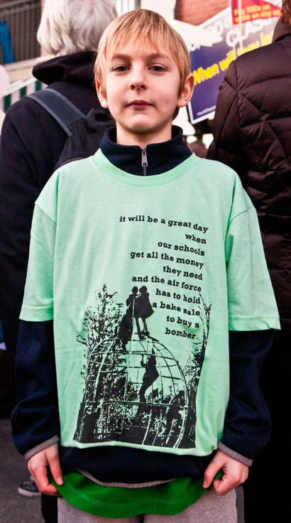 "A boy wearing a tshirt which reads ""it will be a great day when our schools get all the money they need and the air force has to hold a bake sale to buy a bomber"