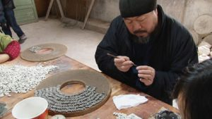 Portrait of Ai WeiWei creating a circular piece of art