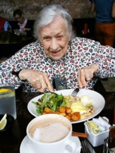 An older woman with knife and fork over a plate of colourful cooked vegs