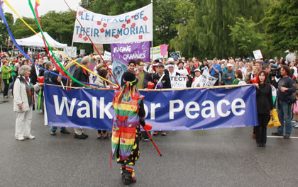 A throng of people march behind the Walk or Peace banner