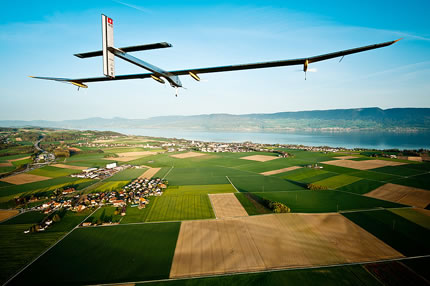 Solar Impulse flying high over river and fields
