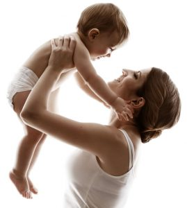 A mother raises her baby fondly into the air.
